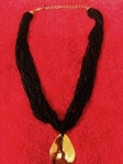Black beaded rope necklace with gold teardrop